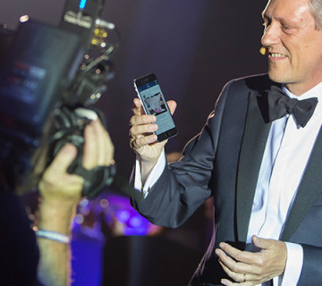 Presenter holds up mobile event app to a camera